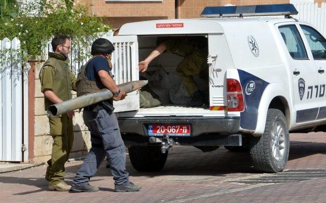Des hommes de la sécurité israéliens transportent un débris d'une roquette à Ashkelon (Crédit : Flash 90)