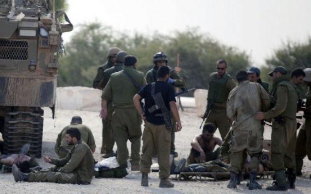 Des soldats aident d'autres soldats blessés pendant l'opération Bordure protectrice (Crédit : Flash 90)