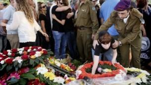 Le fils du Major Amotz Greenberg (rés.), 45, vu sur la tombe de son père lors de l'enterrement au cimetière militaire à Hod Hasharon, le dimanche 20 Juillet 2014. Greenberg a été tué par des terroristes du Hamas sortis d'un tunnel en Israël et ont ouvert le feu sur son véhicule de l'armée le 19 Juillet (crédit photo: Miriam Alster/Flash90).