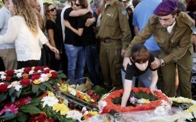 Le fils du Major Amotz Greenberg (rés.), 45, vu sur la tombe de son père lors de l'enterrement au cimetière militaire à Hod Hasharon, le dimanche 20 juillet 2014. Greenberg a été tué par des terroristes du Hamas sortis d'un tunnel en Israël et ont ouvert le feu sur son véhicule de l'armée le 19 juillet (Crédit : Miriam Alster/Flash90).