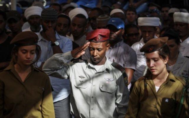 Un soldat éthiopien salue la tombe du soldat Golani, Moshe Malko, au cimetière militaire de Har Herzl à Jérusalem, le 21 Juillet 2014. Moshe Malko, 20 ans, de Jérusalem, a été tué lors des combats dans la bande de Gaza. (Crédit : Hadas Parush/Flash90)