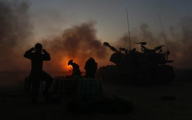 Des soldats israéliens en train de tirer des obus à Gaza, près de la frontière dans le sud d'Israël le 21 Juillet 2014, le au quatrième jour de l'invasion terrestre israélienne dans la bande de Gaza afin de détruire l'infrastructure des tunnels du Hamas, et le 14e jour de l'opération Bordure protectrice (Crédit : Yonatan Sindel/Flash90)