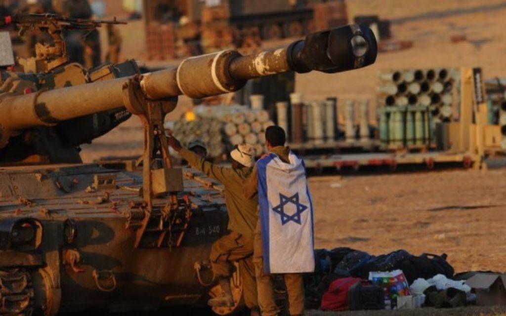 Des soldats israéliens près d'un char d'artillerie dans la bande de Gaza (Crédit : Mendy Hechtman/Flash90)