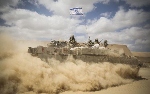 Un APC passe à travers les serres abandonnées près de la frontière israélienne avec Gaza le 25 juillet 2014, alors que les forces israéliennes se rassemblent pour entrer à Gaza. (Crédit : Hadas Parush/FLASH90)