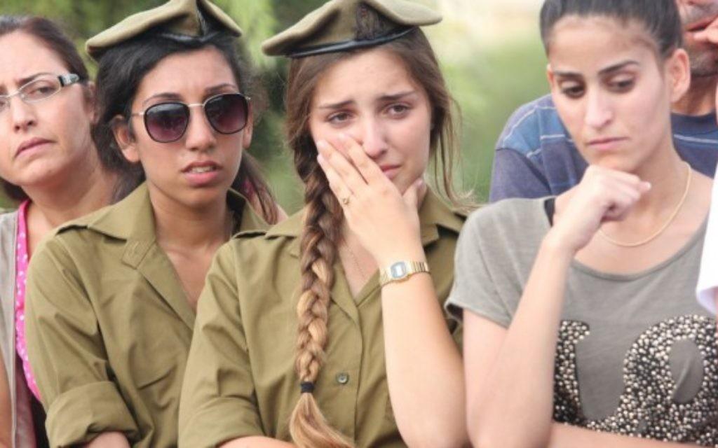Des soldates israéliennes pleurent aux funérailles du sergent soldat israélien. Adar Bersano, 20 ans, tué alors qu'il luttait contre un groupe de militants palestiniens qui se sont infiltrés en Israël à travers un tunnel du centre de la bande de Gaza, lors de ses funérailles dans la ville de Nahariya, près de Tel Aviv, le 20 Juillet 2014. (crédit photo: FLASH90)