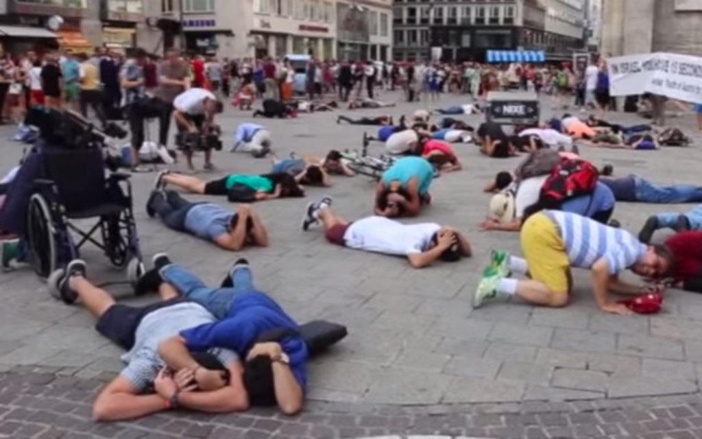 Les gens dans une place principale à Vienne se mettent à couvert pendant un flash mob simulant une attaque de missiles du Hamas le 24 juillet 2014. (Crédit : capture d'écran YouTube)