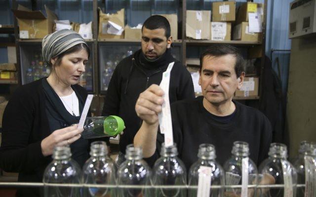 Un ouvrier palestinien et un employé juif de SodaStream dans l'usine du parc industriel de Mishor Adumim, le 2 février 2014. (Crédit : Nati Shohat/Flash90)