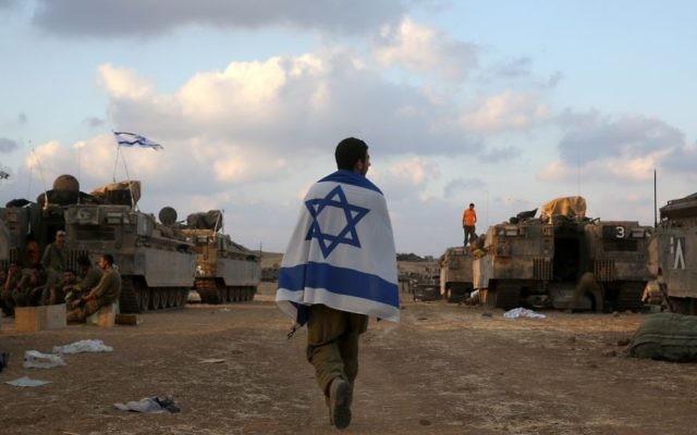 Un soldat israélien porte le drapeau israélien à Gaza - 19 juillet 2014 (Crédit : Nati Shohat/Flash90)
