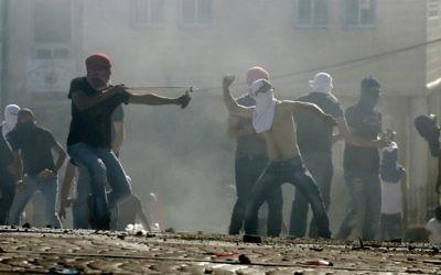 Des Palestiniens masqués en train de jeter des pierres sur la police à Jérusalem Est le 3 juillet 2014  (Crédit : Slimane Khader/Flash90)