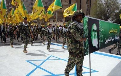 Membres irakiens du Hezbollah tiennent les drapeaux jaunes de la branche irakienne du parti chiite et un portrait de guide spirituel de l'Iran, l'ayatollah Ruhollah Khomeini, et ils marchent sur un drapeau israélien peint sur le sol pendant la journée d'al-Qods (Jérusalem) - 25 Juillet 2014, la capitale irakienne Bagdad. (Crédit : AFP / Ali al-Saadi)