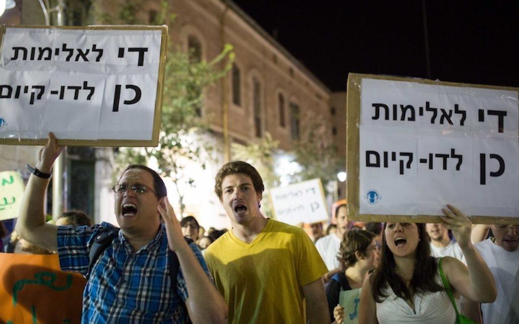 """Les participants à un rassemblement anti-racisme à Jérusalem brandissant des pancartes qui disent : « Assez de violence. Oui à la co-existence,"""" 7 juillet 2014. (Crédit : Noam Revkin Fenton/Flash 90)"""