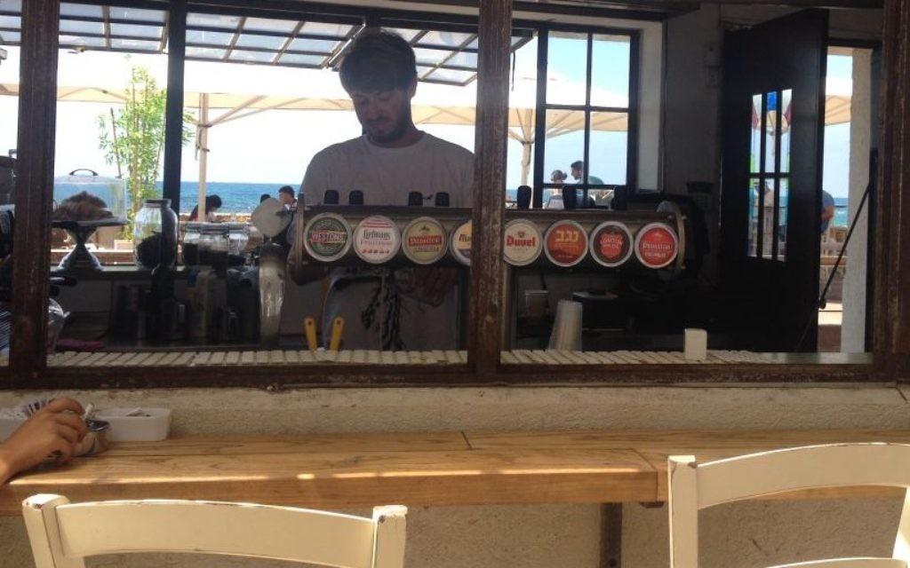 Roi Sterman, un étudiant de l'Université Bar Ilan qui sert au bar au port de Jaffa, dit que l'entreprise a été mauvaise pendant deux mois, mais il y a un flux constant de touristes de la Cisjordanie, pour célébrer l'Aïd al-Fitr (Crédit : Jessica Steinberg / Times of Israël)