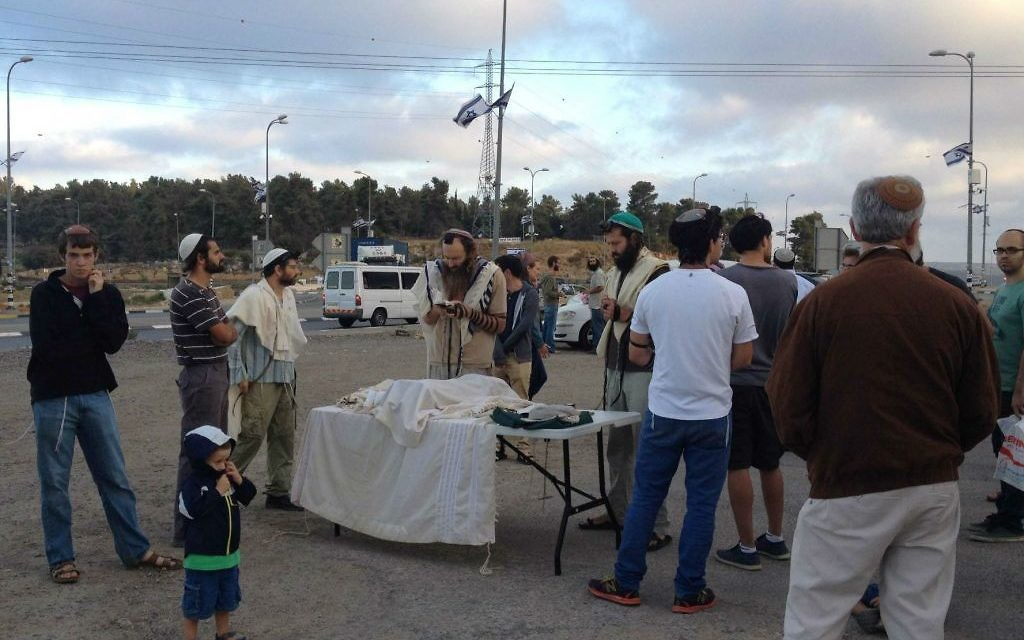 Israéliens réunis pour les prières à l'intersection du Gush Etzion avant de rejoindre les Palestiniens locaux pour un repas en commun pour rompre le jeûne (Crédit : Jessica Steinberg/Times of Israel)