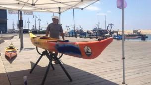 Roni Levinson, instructeur de Kayak est coincé à peindre ses kayaks plutôt que de prendre des clients sur l'eau (Crédit : Jessica Steinberg / Times of Israël)