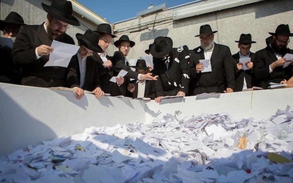 Des hommes prient le jour des 20 ans de l'anniversaire de la mort de Menachem Mendel Schneerson (Crédit : Adam Ben Cohen/Chabad.org)