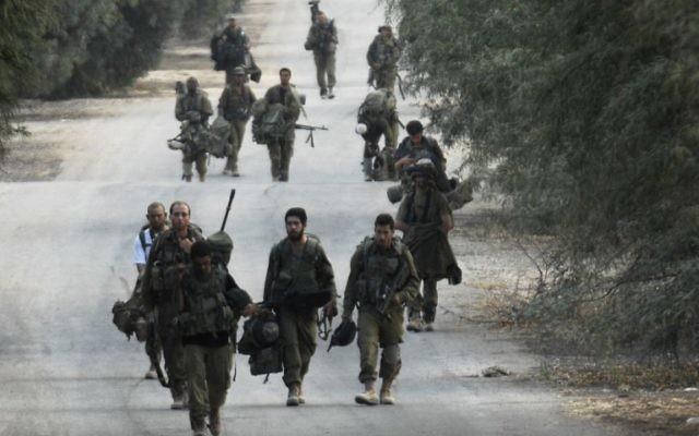 Soldats israéliens à pied près de la frontière entre Israël et la bande de Gaza qui reviennent de l'enclave côtière palestinienne contrôlée par le Hamas, le mardi 5 août 2014 (Crédit : AFP / DAVID BUIMOVITCH)