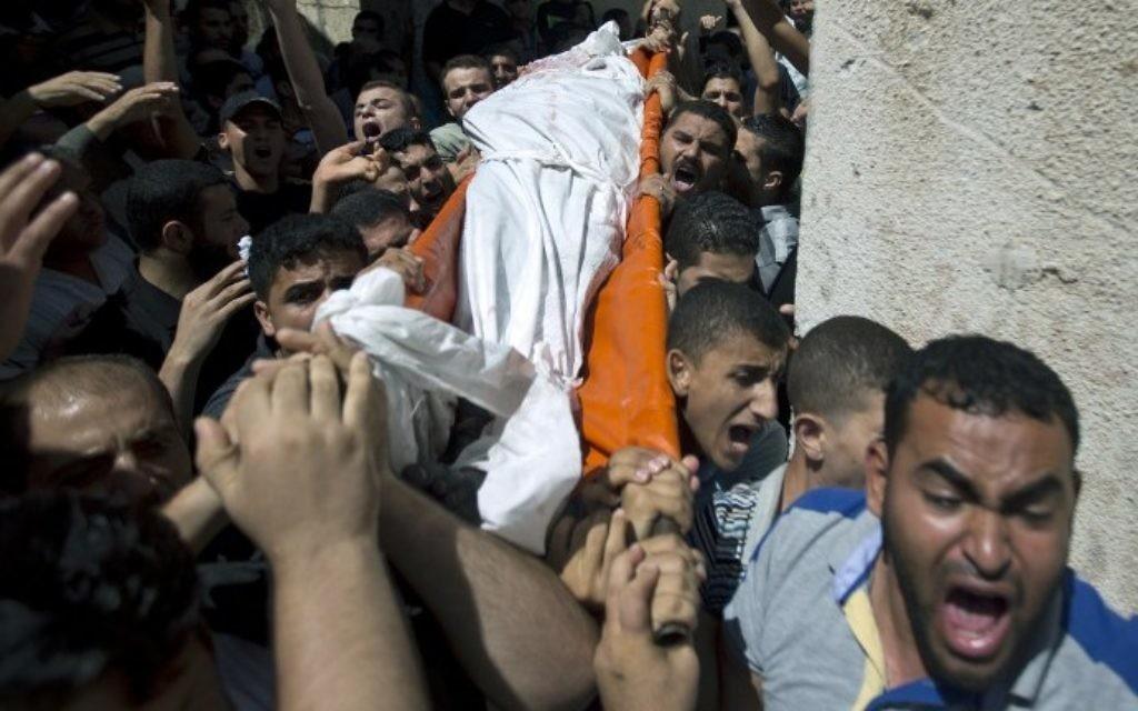 Des Palestiniens portent le corps de l'un des trois commandants du Hamas tués par Tsahal -  l'enterrement s'est déroulé dans le sud de la bande de Gaza à Rafah, le 21 août, 2014 (Crédit : AFP Photo / Mahmud Hams)
