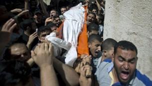 Des palestiniens portent le corps de l'un des trois commandants du Hamas lors de leur enterrement dans le sud de la bande de Gaza à Rafah, le 21 août, 2014 (Crédit : AFP Photo / Mahmud Hams)
