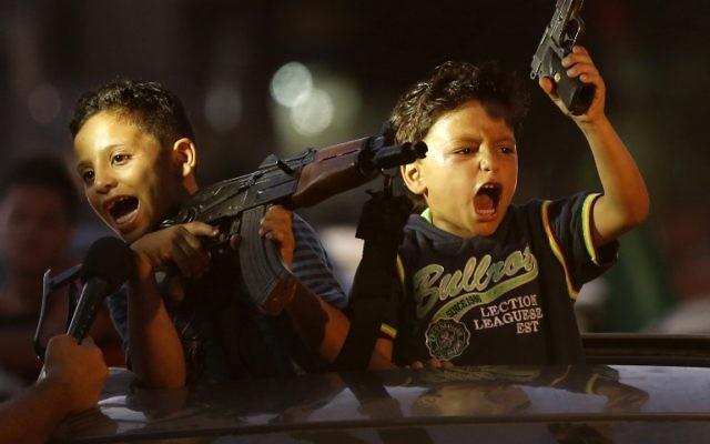 Des enfants lèvent des armes en l'air (dont une avec un chargeur vide) sur une voiture alors que les Palestiniens se rassemblent dans les rues pour célébrer après un accord conclu entre le Hamas et Israël - 28 août 2014 (Crédit : AFP PHOTO / MOHAMMED ABED)