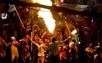 Un Palestinien souffle le feu tandis que les Gazaouis se rassemblent pour célébrer le cessez-le-feu entre Israël et le Hamas le 26 août, 2014  dans la ville de Gaza. (Crédit : AFP PHOTO / ROBERTO SCHMIDT)