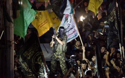 Un militant brandit son arme alors qu'il tire des coups de feu en l'air après avoir rejoint des centaines d'habitants de Gaza, le 26 août 2014 pour célébrer un accord de cessez-le-feu conclu entre Israël et le Hamas. (Crédit : AFP PHOTO / ROBERTO SCHMIDT)