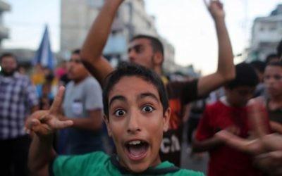 """Des Gazaouis fêtent la """"victoire de la résistance"""" face à Israël pendant l'opération Bordure protectrice - 26 août 2014 (Crédit : AFP)"""