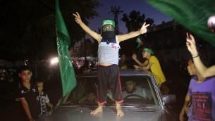 Un enfant palestinien avec un bandeau du Hamas fait le signe de la victoire sur une voiture alors que les gens se rassemblent dans les rues pour célébrer l'accord de trêve conclu entre le Hamas et Israël, à Rafah, dans le sud de la bande de Gaza, le 26 août, 2014. (Crédit : AFP PHOTO / SAID KHATIB)