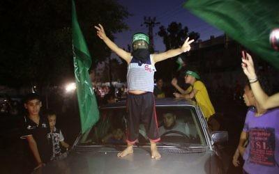 Un enfant palestinien avec un bandeau du Hamas fait le signe de la victoire sur une voiture alors que les gens se rassemblent dans les rues pour célébrer l'accord de trêve conclu entre le Hamas et Israël, à Rafah, dans le sud de la bande de Gaza, le 26 août 2014. (Crédit : AFP PHOTO / SAID KHATIB)