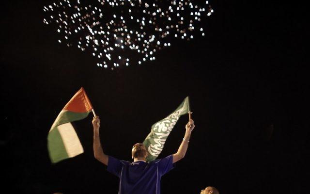 Des Palestiniens tiennent un drapeau palestinien et un drapeau du Hamas alors que des feux d'artifice illuminent le ciel le 26 août, 2014 à Jérusalem-Est (Crédit : AFP PHOTO / AHMAD GHARABLI
