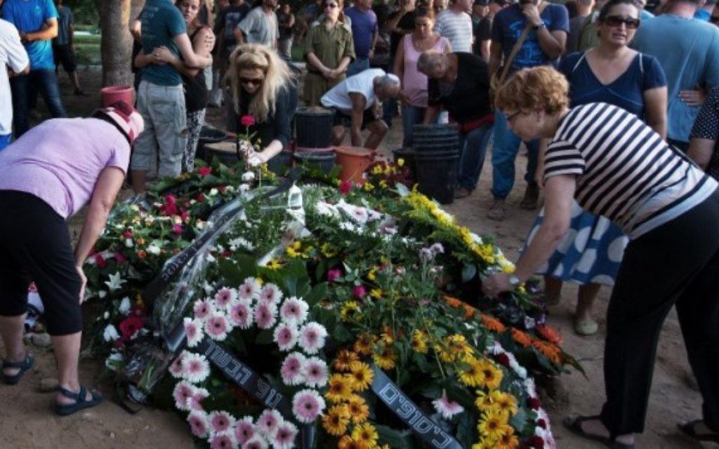 Des Israéliens déposent des couronnes de fleurs sur la tombe de Shahar Melamed, 43 ans, qui a été tué la veille par un tir de mortier palestinien dans le kibboutz Nirim près de la frontière d'Israël avec la bande de Gaza, le 27 août 2014 (Crédit : AFP / MENAHEM KAHANA)