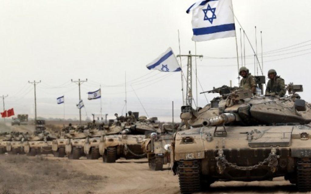 Les chars israéliens Merkava roulent près de la frontière entre Israël et la bande de Gaza d'où ils reviennent, le 5 Août 2014, après qu'Israël a annoncé que toutes ses troupes s'étaient retiré. (Crédit : AFP / THOMAS COEX)