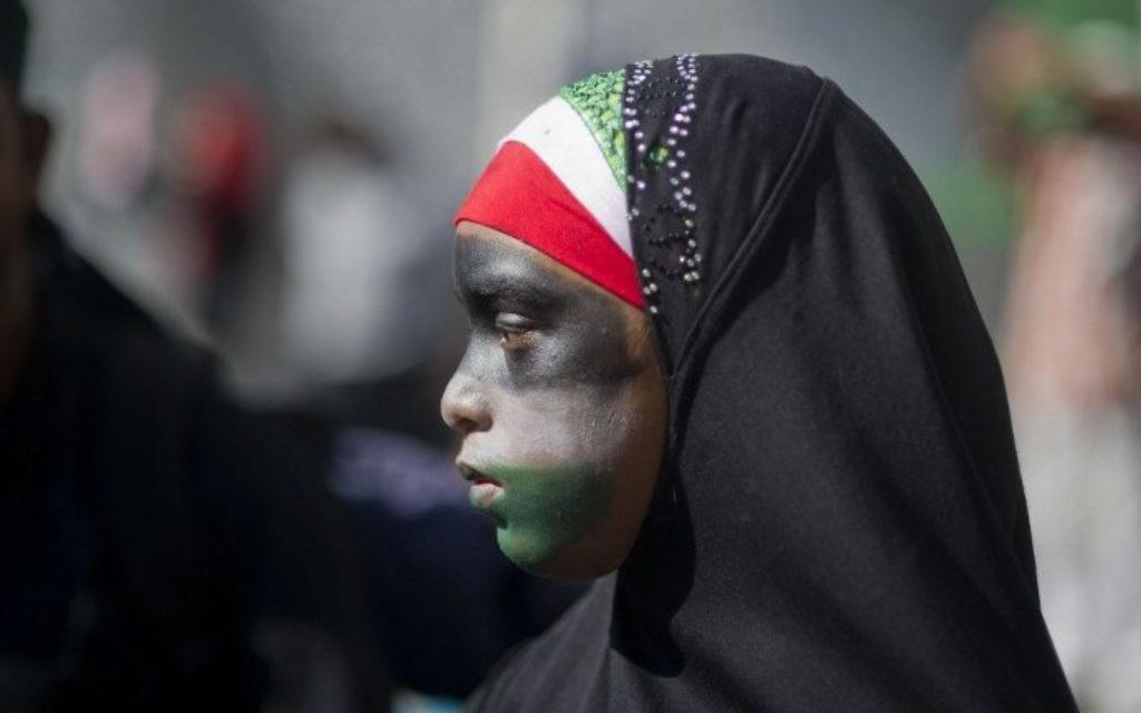Une jeune fille portant un hijab, avec son visage peint aux couleurs du drapeau palestinien, participe à une marche anti-Israël au Cap, en Afrique du Sud le samedi 9 août, 2014 (Crédit : Roger Bosch / AFP)