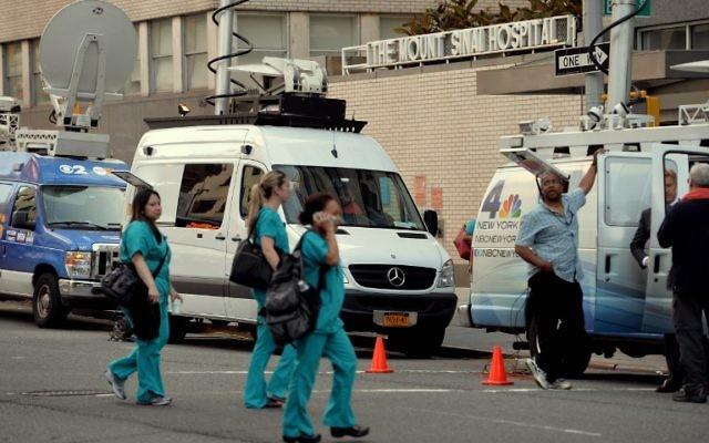 Des camions de télévision en dehors de l'hôpital Mount Sinai Août 4, 2014 New York, après que les autorités ont annoncé qu' n patient qui s'est récemment rendu en Afrique de l'Ouest est actuellement testé pour le virus Ebola. (Crédit : AFP PHOTO / Stan HONDA)