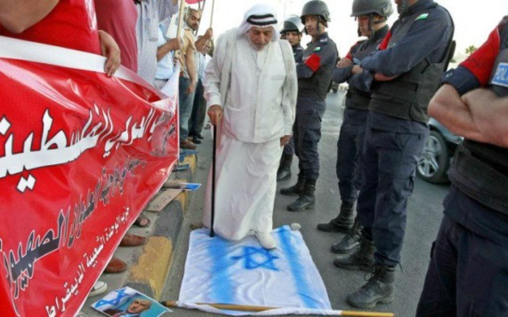 Un manifestant jordanien marche sur un drapeau national israélien. Il prend part à une manifestation devant l'ambassade américaine à Amman, le 3 Août 2014 contre le soutien américain à l'offensive israélienne dans la bande de Gaza. (Crédit : AFP/KHALIL MAZRAAWI)