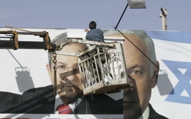 Des ouvriers remplaçant une affiche de campagne du Parti travailliste avec une du Likud à Jérusalem, le 30 janvier 2009 (Crédit : Yossi Zamir / Flash90)