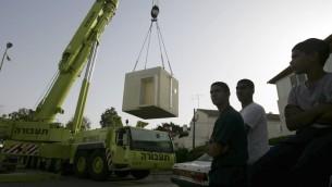 Des travailleurs installant des abris dans les écoles et les crèches d'Ashkelon en 2009 (Crédit : Edi ISrael/Flash90)