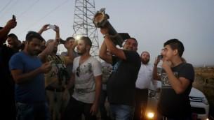 Les résidents de Sderot regardant un morceau d'une roquette qui est tombée dans un champ ouvert (Crédit : Miriam Alster / flash 90)