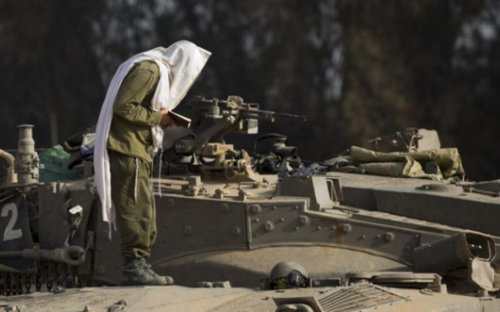 Un soldat israélien prie depuis la bande de Gaza lors de l'Opération Bordure protectrice (Crédit : Yonatan Sindel/Flash 90)