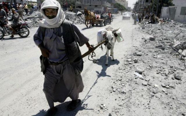 Des Palestiniens quittent leur quartier pour un endroit plus sûr alors que l'armée israélienne a continué à bombarder la zone de Rafah, dans le sud de la bande de Gaza, le 4 Août 2014 (Crédit : Abed Rahim Khatib/Flash90).