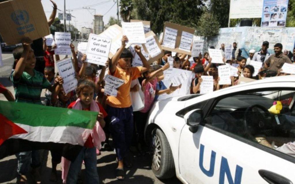 Des enfants palestiniens manifestent devant une école de l'UNRWA (Crédit : Flash 90)
