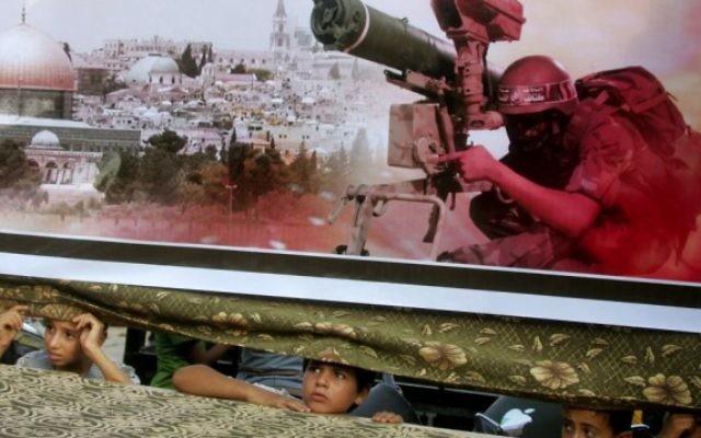 Des enfants palestiniens regardent de derrière une banderole lors d'un rassemblement pro-Hamas à Rafah, au sud de la bande de Gaza, le 17 Août 2014 (Crédit : Abed Rahim Khatib / Flash90)