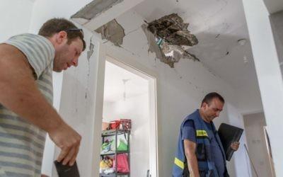 Des travailleurs de l'autorité fiscale évaluent les dommages causés à une maison après avoir été touchée par une roquette au Conseil régional Hof Ashkelon le 20 août, 2014 (Crédit : Flash90)