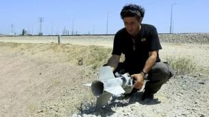 Un homme tient une partie d'une roquette qui a explosé et est tombée à l'intérieur de la frontière israélienne avec la bande de Gaza le 20 août, 2014 (Crédit : Edi Israël / Flash90)