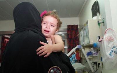 Hala Arada, âgée de deux ans,  avec sa grand-mère Haniyeh Shaer à l'hôpital Wolfson à Holon, le 12 août 2014. Hala a une maladie cardiaque congénitale et est traitée en Israël. Deux membres de sa famille ont récemment été tués dans un raid aérien israélien à Gaza. (Crédit : Sheila Shalhevet / Save a Child's heart)