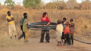 Une étudiante de Ben Gurion Université roule un tuyau d'eau avec quelques habitants après un essai de pompage dans sud de la Zambie, juillet 2011 (Crédit : Noam Weisbrod / Université Ben-Gourion du Néguev)