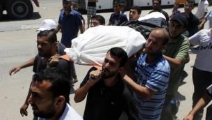 La famille et les amis palestiniens portant le corps d'Hazem Abu Shamalah, 25 ans, pendant ses funérailles à Khan Yunis dans le sud de la bande de Gaza le 27 juillet 2014 (Crédit : Abed Rahim Khatib/Flash90)