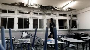 La police examine une salle de classe endomagée par une roquette en novembre 2012 (Crédit : Tsafrir Abayov/Flash90)