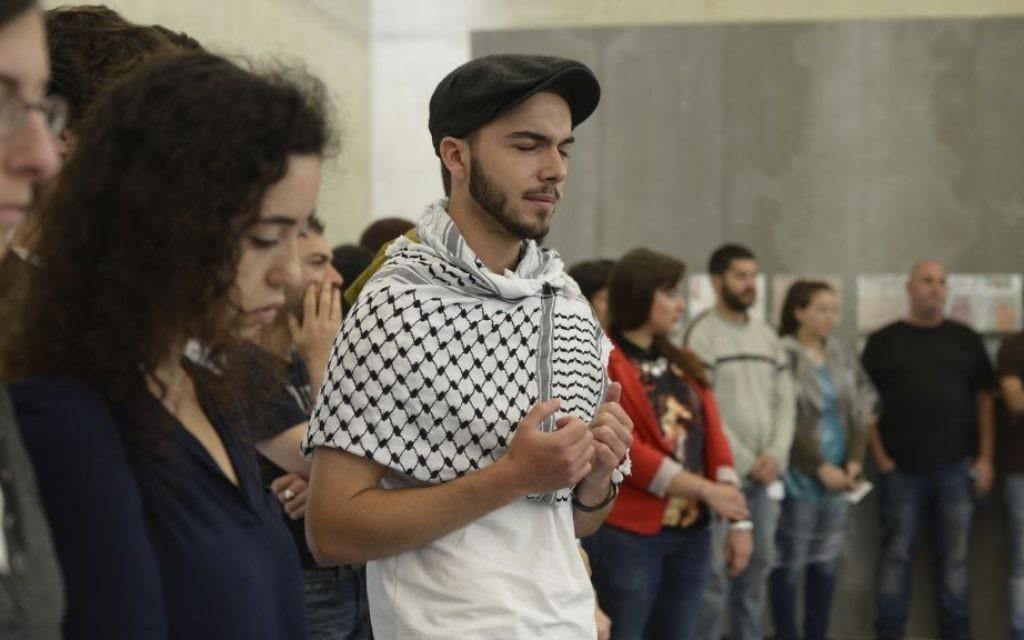Un groupe de participants récite les prières de deuil en Hébreu et en Arabe au camp de Mauthausen (Crédit : Daniel Shaked)