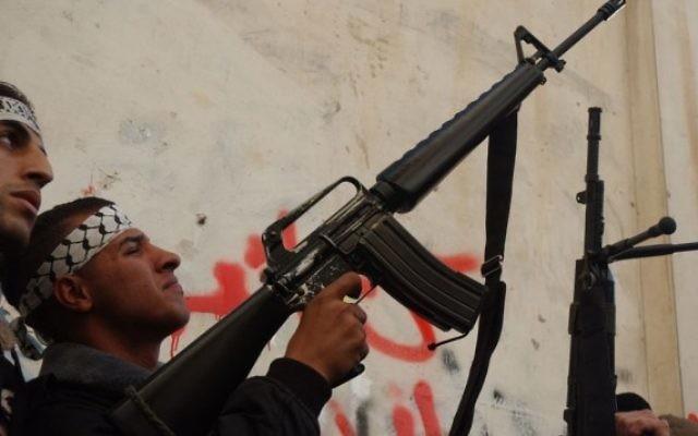 Un Palestinien masqué des Brigades des martyrs d'al-Aqsa, une branche armée du mouvement Fatah du président de l'AP Mahmoud Abbas, détient une arme tout en parlant aux médias à Balata  - camp de réfugiés près de Naplouse, février 2008 (Crédit : Wagdi ASHTIYEH / Flash90 )