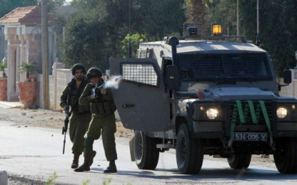 Un soldat israélien tire des gaz lacrymogènes sur les Palestiniens lors d'affrontements suite à une manifestation contre l'offensive militaire israélienne dans la bande de Gaza, le 15 août, 2014 dans le village de Cisjordanie de Silwad, près de Ramallah (Crédit : AFP / Abbas Momani)
